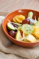 heerlijke fruitsalade in plaat op tafel close-up foto