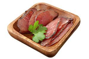 droog gezouten plakjes varkensvlees op houten schotel, over wit. foto