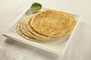 gewone paratha puri geserveerd met vers in blokjes gesneden koriander in het groen foto