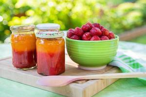zelfgemaakte aardbeienjam in verschillende potten en verse rijpe aardbeien foto