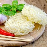 noedels rijst gedraaid met kruiden en basilicum aan boord foto