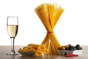 spaghetti, olijven, chili pepers en witte wijn op wit wordt geïsoleerd foto