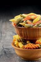rauwe eliche en penne tricolori pasta in de houten kommen foto