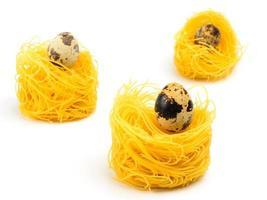drie Italiaanse ei pasta nest op witte achtergrond.