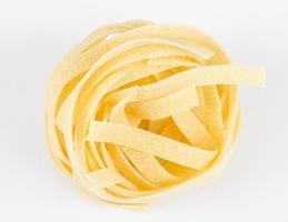 Italiaanse pasta fettuccine nest geïsoleerd op een witte achtergrond foto