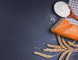 brood, meel en tarwe oren op het zwarte bord foto