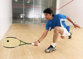 een squashspeler knielt neer om een bal te raken