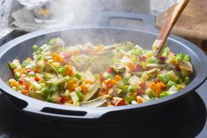 het koken van groenten op een zwarte pan foto