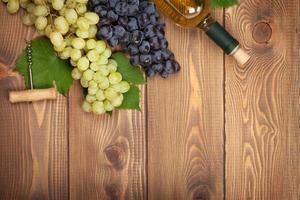 fles witte wijn en tros druiven foto
