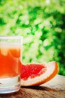 rijp grapefruit met sap op tafel close-up. foto