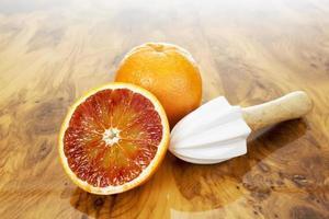 grapefruits, fruitpers met houten handvat op hout foto