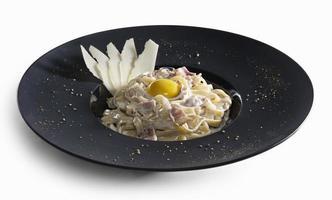 Pasta Carbonara versierd met plakjes Parmezaanse kaas en dooier geïsoleerd foto