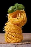 toren van droge pasta nest close-up met groene basilicum foto