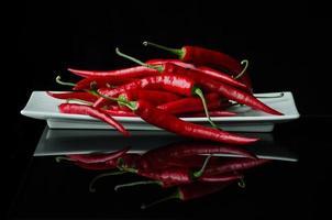 veel chili pepers op zwarte achtergrond foto