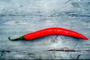 rode peper op een grijze gebruikt houten tafel foto