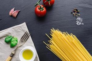 pasta ingrediënten op zwarte leisteen foto