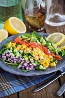 Salade van zalm, avocado, mais, komkommer en ui foto