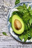 rauwe verse babyspinazie en gesneden avocado op vintage plaat.