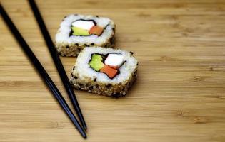 bruine rijst sushi met stokjes foto