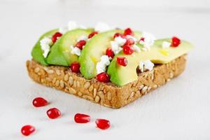 avocado met feta, granaatappel op broodje zonnebloempitten foto