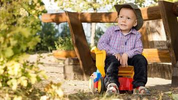 jonge jongen zit in een speelgoed kipper foto