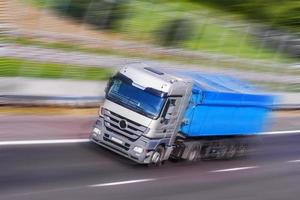 grijs-blauwe vrachtwagen loopt, bewegingsonscherpte foto
