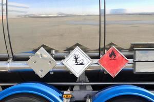 close-up van waarschuwingsborden op de zijkant van zilveren tankwagen foto