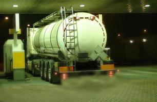 vrachtwagen tanker op een tankstation in de nacht, foto
