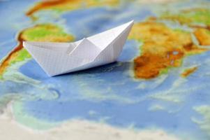 papieren boot op een achtergrondkaart van de wereld foto