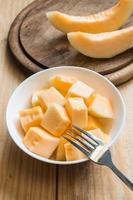 meloen in witte schotel met vork foto