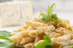 Italiaanse pasta penne gorgonzola en pijnboompitten foto