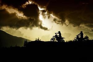 twee motorcrossers op de top van een heuvel foto