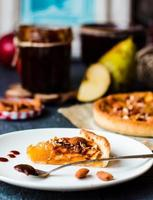 stuk appeltaart op een rond bord, lepel karamel foto