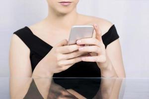 vrouw te typen op een mobiele telefoon foto
