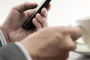 zakenman met behulp van mobiele telefoon met koffiekopje foto