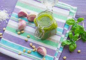 groene pesto in een glazen pot en ingrediënten foto