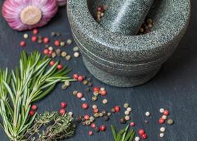 mix van verschillende paprika's in een vijzel, knoflook en kruiden. foto
