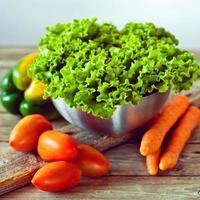 sla salade in metalen kom, tomaten en wortelen foto