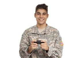 gelukkig soldaat sms'en op mobiele telefoon foto