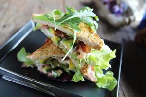 sandwiches met ontmoeten en groenten op houten achtergrond foto