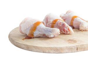 rauwe kippenpoten op houten snijplanken op witte achtergrond foto