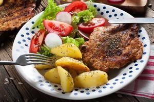 gegrild vlees met salade en geroosterde aardappelen.