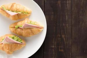 croissant met parmaham en sla op houten tafel foto