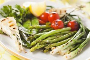 gemarineerde gegrilde groenten - asperges, uien, erwten, tomaten foto