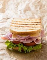 toast ham sandwich op bruin papier foto