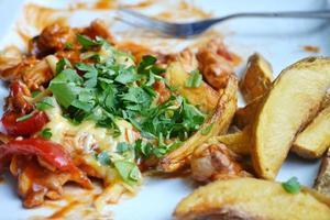 groot bord met gebakken aardappelen, vlees en kaas en saus foto