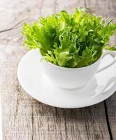 kom verse groene, natuurlijke rucola in witte kop over foto