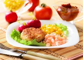 kippenkoteletten met ingeblikte maïs en garnalen.