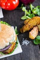 serveert zelfgemaakte hamburger met aardappel wegdes op houten tafel