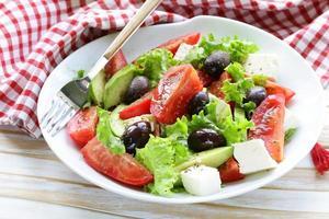mediterrane salade met zwarte olijven, sla, kaas en tomaten